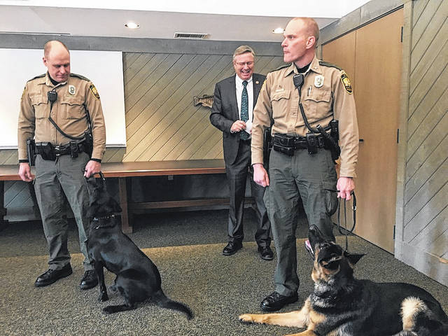 Ohio Department of Natural Resources (ODNR) Director James Zehringer looks on as some of the K-9s from the ODNR Division of Wildlife's new wildlife K-9 program are introduced to the public. From left are: Matt Leibengood, wildlife officer for Sandusky County, with May, and Jeremy Carter, wildlife officer for Holmes County, with Finn.