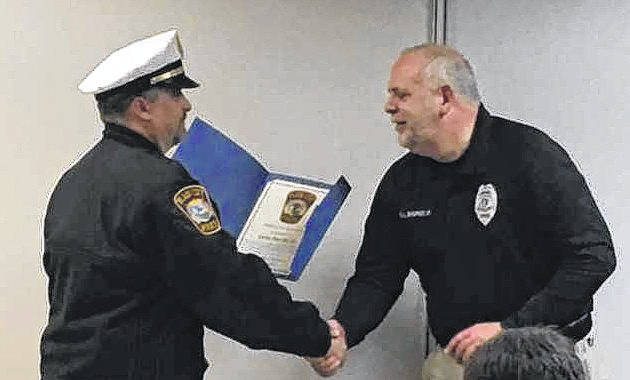 Plain City police chief Dale McKee, left, congratulates officer Gary Sigrist, right, for his dedication to the community at Monday's village council meeting.