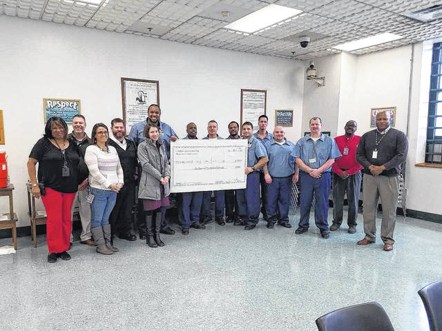 Inmates and officials of London Correctional Institute present a check of $1,500 to the Family Violence Prevention Center of Greene County. Executive Director for the center, Debbie Matheson, accepted the check on Jan. 23.
