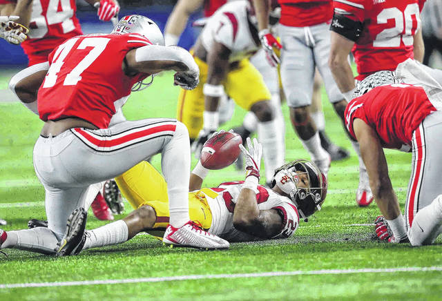 Ohio State linebacker Justin Hilliard (47) celebrates with teammate Austin Mack after they made a tackle on a kickoff return by USC's Velus Jones (23) in the Cotton Bowl at AT&T Stadium Dec. 29.