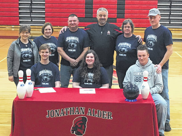 Jonathan Alder senior bowlers sitting from left: Josh Schrock, Hallie Nichols and Zach Otto, are joined by their families and Alder bowling coach Rusty Walter, fourth from left standing, during the college signing held at the high school. All three athletes will continue their bowling careers at Shawnee State University.