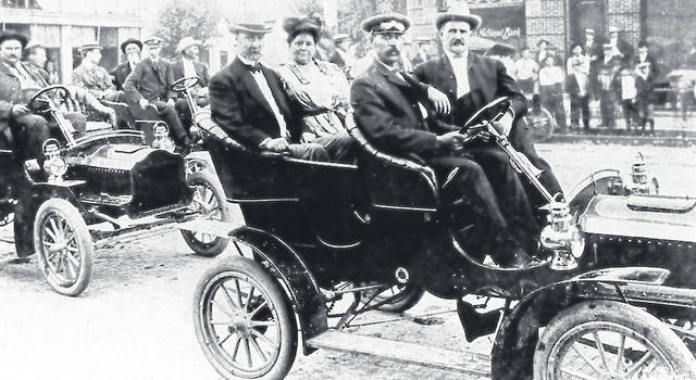 Vice President Charles Fairbanks and his wife Cornelia visit Plain City in 1905. The driver of their car is Calvin Liggett and the passenger is Dr. E. C. Robinson, local dentist. The Farmers National Bank can be seen in the background.