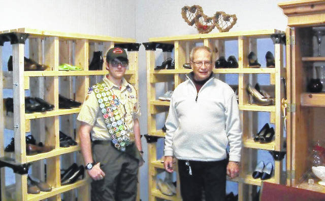 Jon Santini III, left, and Ray Meister of the Plain City Food Pantry, stand among the shelving built for the pantry's Thrift Store as part of Santini's Eagle Scout project.