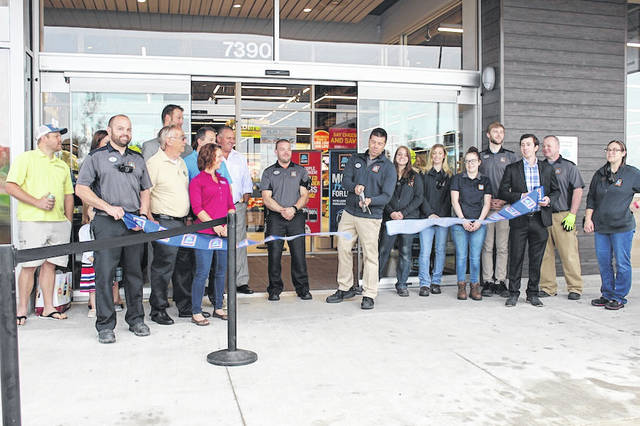 Plain City village officials and Aldi employees look on as the ribbon is cut, marking the new store's opening Friday morning.