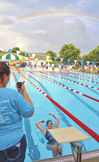 London's Kaitlyn Adkins takes off from the starting blocks amid a rainbow-filled sky Wednesday evening at Plain City Aquatic Center. Adkins' team — the Madison Marlins — along with the Plain City Sharks, were among the squads to participate in the evening's swim meet.