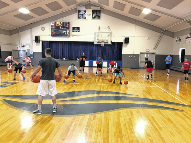 Campers go through dribbling drills during the Flames summer basketball camp at Shekinah Christian School.